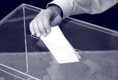 Its time for elections. Image of a ballot box and hand putting a blank ballot inside, elections concept stock photos