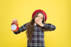 Its time to go to sleep. Sleepy little girl in evening time on yellow background. Yawning small child holding alarm. Clock. Late time. Break time, refresh stock photos