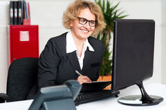 Its time to work. Front desk lady making notes. Female secretary wearing eyeglasses holding pen and looking at computer screen Stock Photography