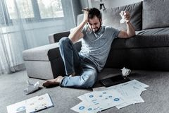 Depressed angry man not coping with his work. Its too much. Depressed angry young man sitting on the floor and being surrounded by papers while not coping with Royalty Free Stock Photo