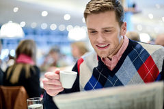 Its very interesting news today. Handsome man reading daily at outdoor cafe stock photos