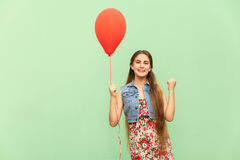 Its winn! The beautiful blonde teenager with red balloons on a green background. Stock Photos