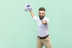 Its for you! Young adult businessman, holding gift box, pointing finger at camera and toothy smile. Isolated on light green backgr. Ound. Indoor, studio shot Royalty Free Stock Images