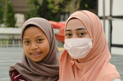 Two girls in hijab, one of them wearing a mask royalty free stock images
