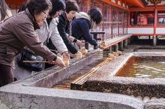 ITSUKUSHIMA HEILIGDOM, Japanse mensen die hand wassen Royalty-vrije Stock Fotografie