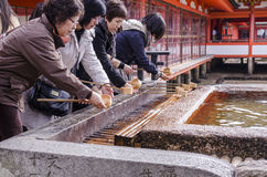 ITSUKUSHIMA-SCHREIN, japanisches Volk, das Hand wäscht Lizenzfreie Stockfotografie