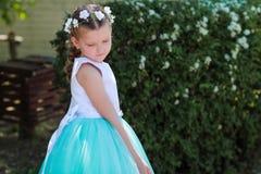 Ittle女孩是害羞的并且看得下来,在有人造花花圈的蓝色和白色礼服打扮的Ñ 犹特人小女孩在她的头的 免版税库存图片