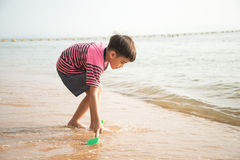ittle boy playing sand on the beach summer time Royalty Free Stock Image