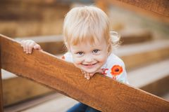 Ittle caucasiangirl palaing hide and seek. 1 year old little caucasiangirl palaing hide and seek game outdoors on sunny warm summer day. Closeup portrait of Royalty Free Stock Photography