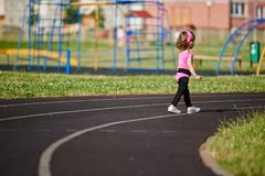 Ittle cute girl running at stadium Stock Images