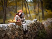 Ittle girl with big dog in the forest in autumn. Sad little girl with big dog in the forest in autumn Stock Photos