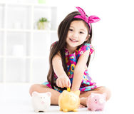 Ittle girl playing with piggy bank Stock Photography