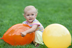 Ittle girl playing with yellow and red balloons Royalty Free Stock Image