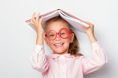 Ittle girl preschooler wearing glasses keeps an open book on her head stock photography