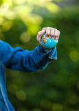 Ittle girl squeezing Earth globe at hand Stock Photography