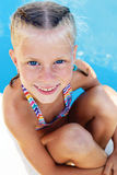 Ittle girl vacationers beside swimming pool. Portrait of a little girl vacationers beside swimming pool in a sunny summer day Royalty Free Stock Image