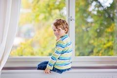 Ittle-Kinderjunge, der nahe Fenster sitzt und auf Herbstbäumen schaut Lizenzfreies Stockbild