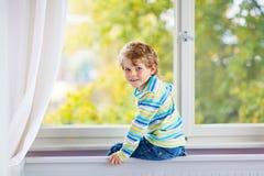 Ittle-Kinderjunge, der nahe Fenster sitzt und auf Herbstbäumen schaut Stockbild