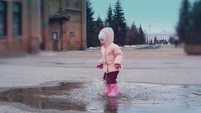 : ittle springt het kind in een vulklei, verlatend partij van nevel stock video