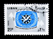 ITY Emblem and Cedars, International Tourist Year 1967 (II) serie, circa 1967. MOSCOW, RUSSIA - MARCH 18, 2018: A stamp printed in Lebanon shows ITY Emblem and stock photos