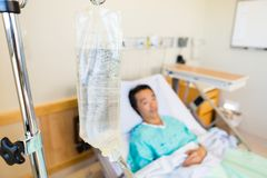 IV Bag With Patient Lying On Hospital Bed Royalty Free Stock Photography