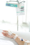 IV solution in a patient hand with IV machine Royalty Free Stock Images