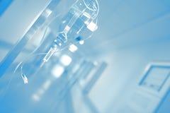 Iv-Tropfenfänger in unscharfer Krankenhaushalle Lizenzfreie Stockfotos