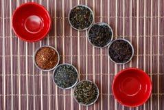 Ivan te, rooibos marrakech, svart te, grönt te och röda koppar på en matt brun bambu Royaltyfri Fotografi