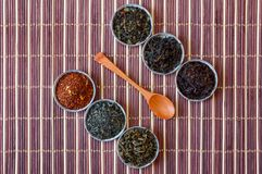 Ivan tea, rooibos marrakech, black tea, green tea and wooden spoon on a brown bamboo mat, top view. Close-up Royalty Free Stock Image