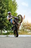 Sideview of biker riding motorcycle in extreme way. Ivano-Frankivsk, Ukraine - 28 August 2015 : Amazing sideview of young biker riding his sport motorcycle on stock photo