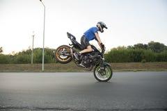 Biker practising his skillsin making stunts. Stock Images