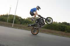 Brave biker standing on motorcycle during riding. Stock Photo
