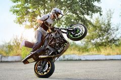 Biker is riding motorcycle in extreme way. royalty free stock photo
