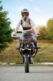 Frontview of young strong biker sitting on sport motorcycle. Ivano-Frankivsk, Ukraine - 28 August 2015 : Young extreme biker looking at camera sitting on sport royalty free stock image