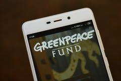 Greenpeace logo seen on the smartphone screen. Ivano-Frankivsk, Ukraine - May 9, 2019: Greenpeace logo, on the smartphone screen. Greenpeace website displayed on royalty free stock photos