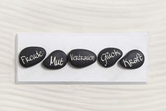 Ive black stones with german text for happiness, courage, trust,. Luck and power. Concept for work-life-balance Royalty Free Stock Photos
