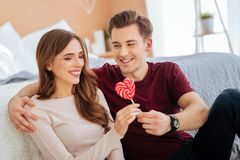 Radiant girl receiving heart shaped lollipop from girlfriend Stock Photo