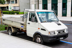 Iveco Daily. GENEVA, SWITZERLAND - AUGUST 4, 2014: White flat-bed cargo truck Iveco Daily in the city street royalty free stock photos