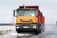 Iveco Trakker. NOVYY URENGOY, RUSSIA - MAY 2, 2014: Orange Iveco Trakker dump truck at the interurban road royalty free stock images