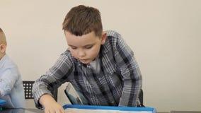 Ivestigate feliz de los muchachos y discutir el proceso que dirige en la lección del aprendizaje electrónico en la cámara lenta d metrajes