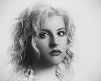 Ivory. Closeup B&W portrait of a beautiful young woman with blond curly hair and a memorable expression Stock Images