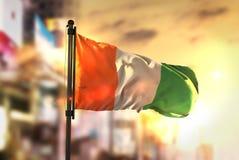 Ivory Coast Flag Against City Blurred Background At Sunrise Back Stock Photo