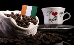 Ivory Coast flag in a bag with coffee beans  on black Stock Photo
