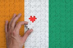 Ivory Coast flag is depicted on a puzzle, which the man`s hand completes to fold.  stock illustration