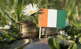 Ivory Coast flag with stack of money coins with grass Royalty Free Stock Image