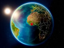 Ivory Coast with sunset from space. Sunset above Ivory Coast highlighted in red on planet Earth with visible country borders. 3D illustration. Elements of this stock photos