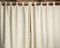 Ivory curtain hanging on a metal rod. With the help hinges Stock Image