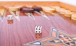Ivory dices on handmade backgammon board isolated Royalty Free Stock Image