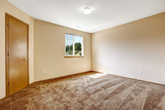 Ivory empty room with brown carpet floor and wooden door Royalty Free Stock Image