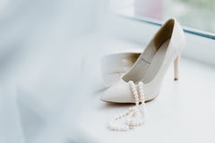 Ivory female wedding footwear with pearls juweliry on the window Stock Images